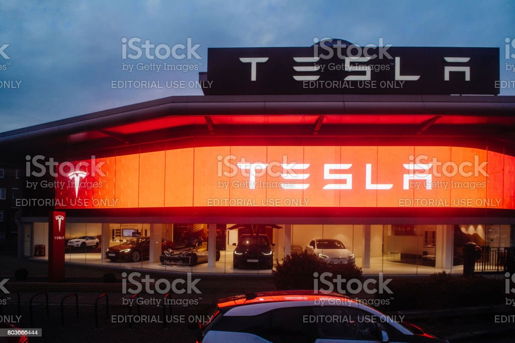 Street view of Tesla motors showroom with cars inside and illuminated logo brandin at dusk London UK stock photo