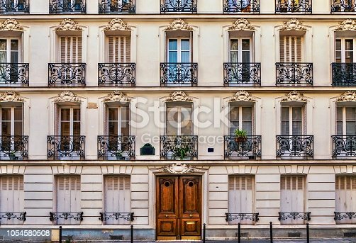 Beautiful old Parisian residential building, with traditional full length windows and exterior ornate wrought iron railings. The main entrance has an elegant, wooden door.
