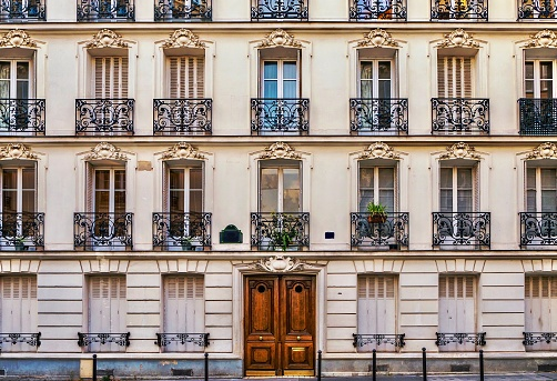 Street view of the elegant facade of an old apartment building in a residential neighborhood of Paris. Vintage style photo.