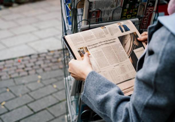 straßenansicht der frau kaufen ft wochenende zeitung - zeichen lesen stock-fotos und bilder