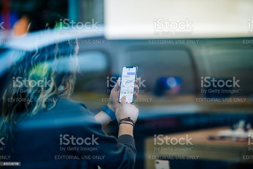 Street view of woman trying Animoji on latest iPhone X in Apple Store stock photo