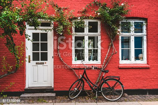 Copenhagen, Denmark -September 23th, 2015. Street, wall and bike. White color windows, door and modern bicycle leaned to red wall with blossom flowers.