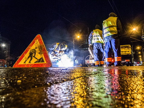 Low angle view of street workers and a welder while repairing the rail tracks in the city at night. Road sign is in front and truck with equipment is in the background.