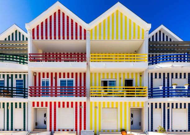 Straße mit bunten Häusern in Costa Nova, Aveiro, Portugal. Straße mit gestreiften Häusern, Costa Nova, Aveiro, Portugal. Fassaden von bunten Häusern in Costa Nova, Aveiro, Portugal. – Foto
