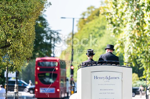 istock Street with horse tour traditional carriage and cars in traffic on road by Kensington during sunny day with sign for Belgravia office 1125781479