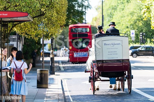 istock Street with horse tour traditional carriage and cars in traffic on road by Kensington during sunny day with bus stop and people 1125782554