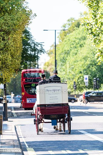 istock Street with horse tour traditional carriage and cars in traffic on road by Kensington during sunny day vertical view 1125783600