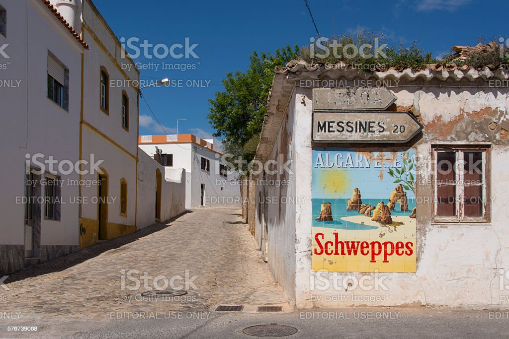 Street with old schweppes advertisement in Portugal