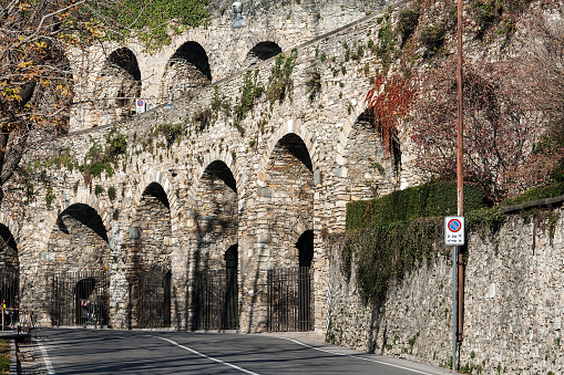 Street with old wall arch ruins in Bergamo town, Italy