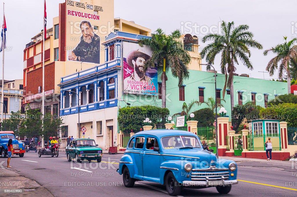 Street with oldtimers and propaganda in Santiago de Cuba stock photo