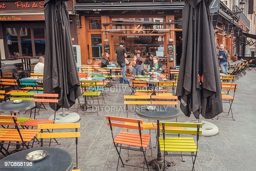 Brussels, Belgium - Apr 9, 2018: Street with outdoor cafe, talking people and old buildings of historical city with restaurants on April 9, 2018. More than 1,200,000 people lives in Brussels