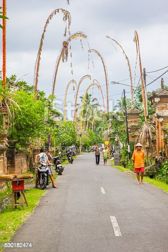 Ubud, Indonesia - January 8, 2011: People walk on a village street decorated with penjors near Ubud, Bali. A penjor is a tall, curved bamboo pole decorated with coconut leaves with an offering at the base. It is used by Hindus in Bali as part of almost every important ceremony.
