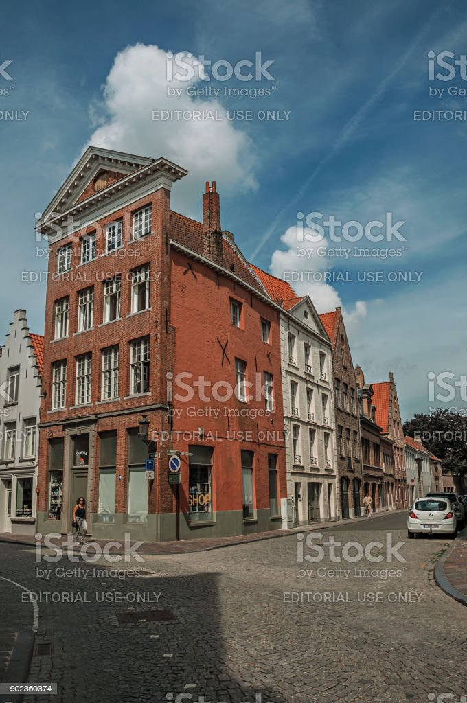 Street with people, brick houses and shops at Bruges. stock photo