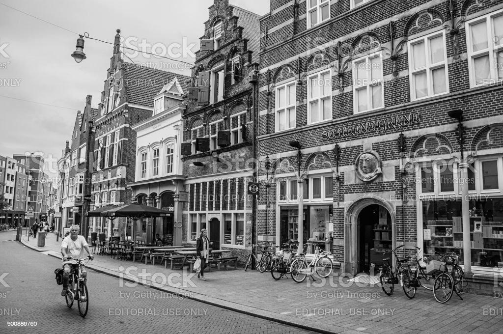 Straat met restaurants, winkels, fietsers en mensen wandelen in's-Hertogenbosch. foto