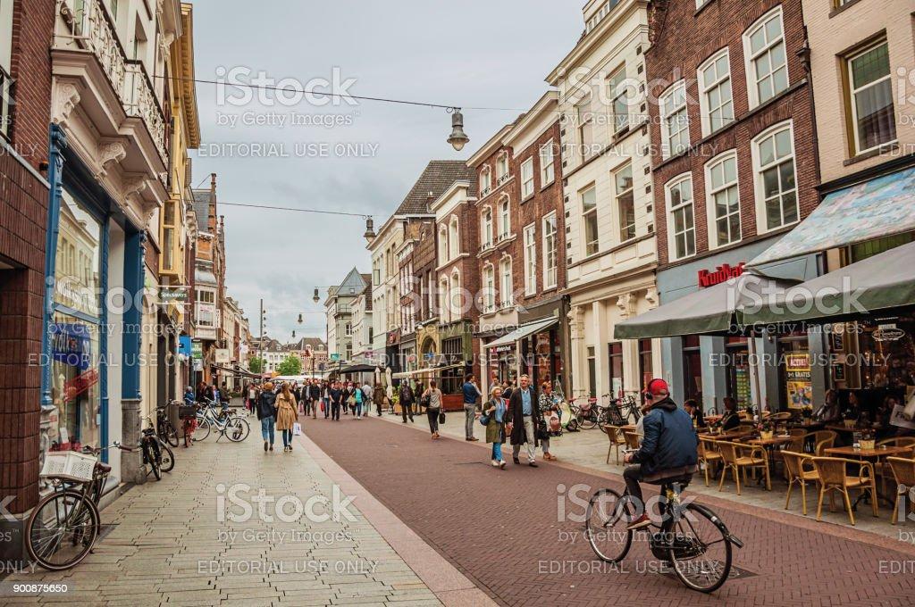 Straat met restaurants, winkels, fietsers en mensen wandelen in de binnenstad van's-Hertogenbosch. foto