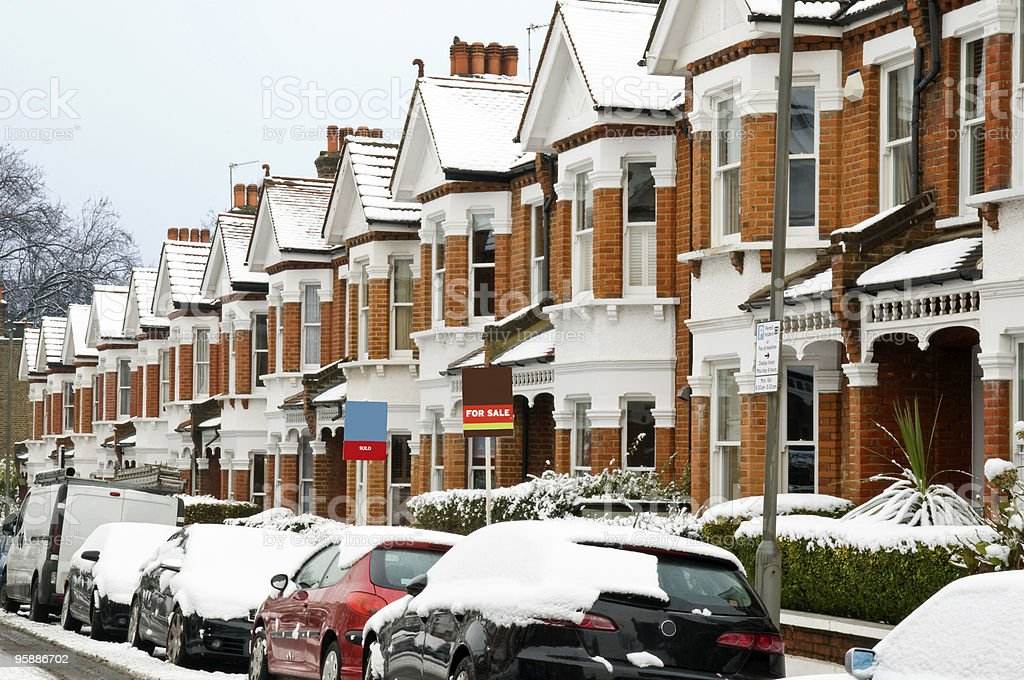 Street with snow covered cars and houses in Winter in London stock photo