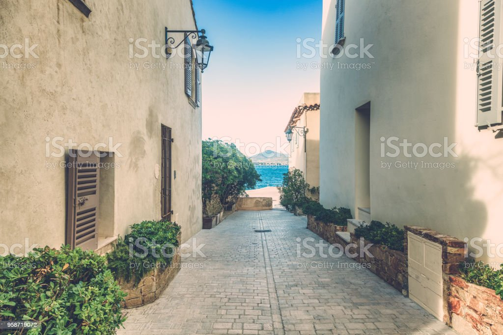 Street with white buildings leading to the sea, Saint Tropez, Provence, France, Cote d'Azur. French style architecture stock photo