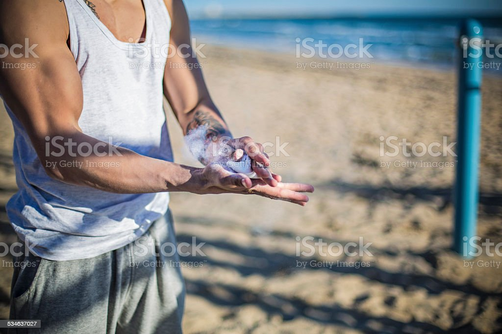 Man practising street workout in the beach dusting chalk on his hands.