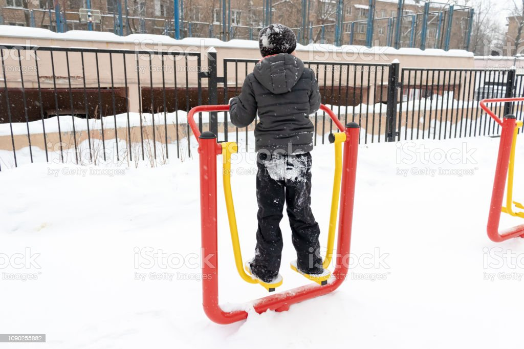 Street workout equipment in winter, outdoor sport fitness and...