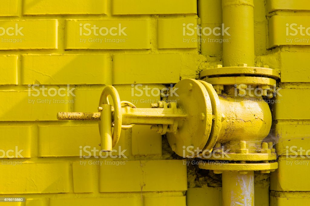 Street yellow gas pipe with valve stock photo