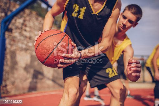 Group of men, basketball players on court outdoors on a sunny day, playing a match.