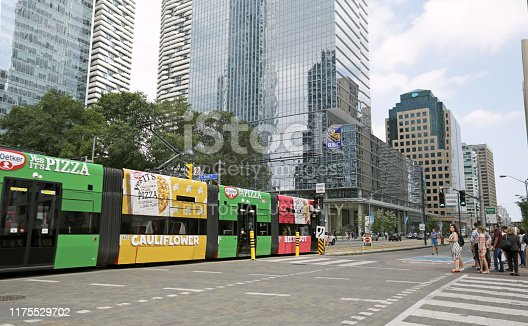 Toronto, Canada - August 21, 2019: Passengers wait for a colourful TTC streetcar along Queens Quay West near York Street on a summer afternoon. Modern residential and office towers line the downtown Harbourfront neighbourhood north of Lake Ontario.