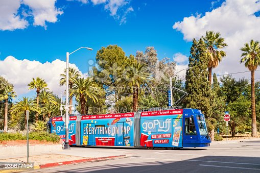 An ad wrapped streetcar moves along a street on the University of Arizona campus in Tucson Arizona USA.