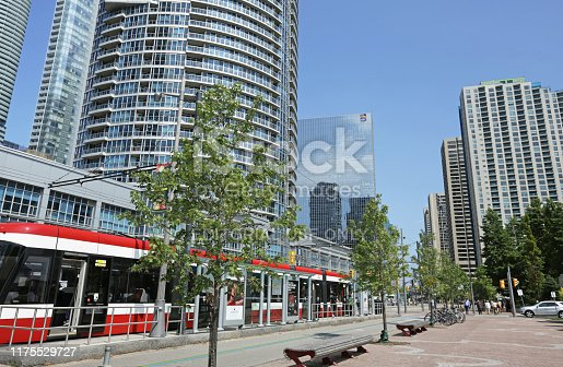 Toronto, Canada - August 21, 2019: A TTC streetcar runs alongside a bike lane on Queens Quay West. Modern residential and office towers line the Harbourfront neighbourhood near Lake Ontario.