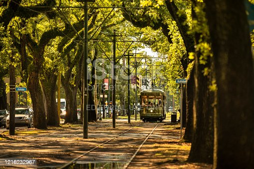 New Orleans, Louisiana - June 18, 2019:  Passengers ride the historic streetcar along Saint Charles Avenue in the Garden District of New Orleans Louisiana USA.  The St. Charles Avenue line is the oldest continuously operating street rail system in the world.