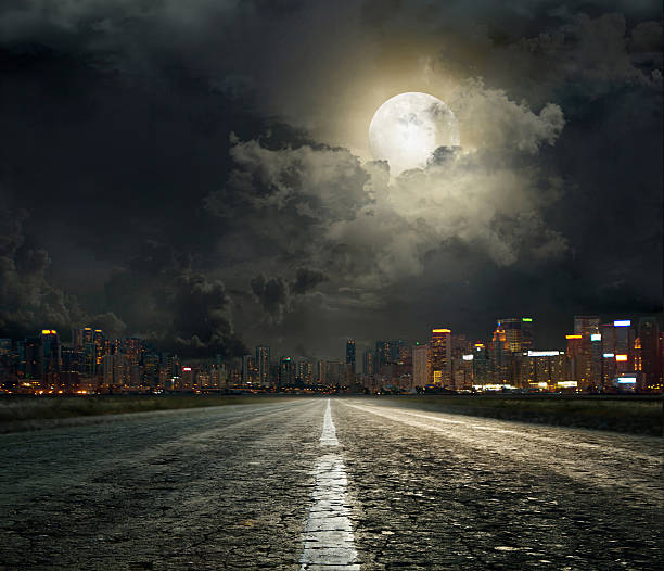 street-level view of a moonlit city road on a cloudy night - city street stock pictures, royalty-free photos & images