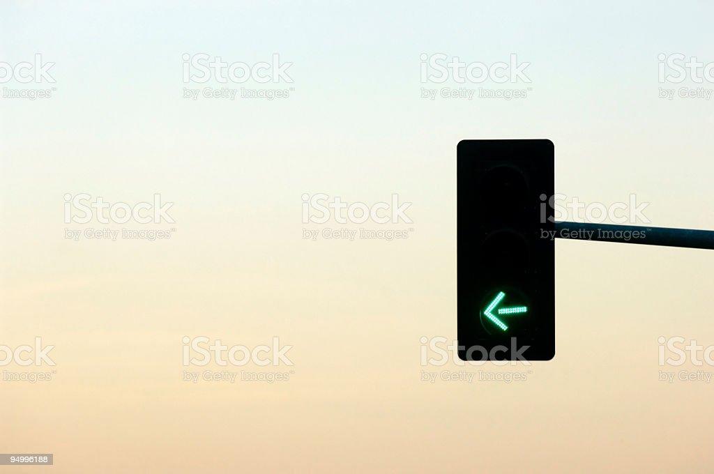Streetlight at dusk with green left arrow stock photo