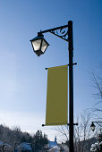 """""""A classic streetlight with a blank, verticle banner."""""""