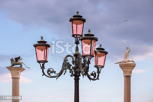 venetian lamppost between the columns of St. Mark's winged lion and St. Theodore statue in Venice, Italy
