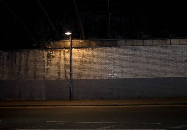 streetlight under the railway bridge, great bridgewater street, manchester, england. - dimly stock pictures, royalty-free photos & images