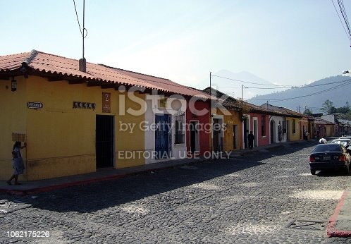 Cobblestone streets by traditional colourful houses in Antigua, Guatemala. Antigua is a town famous for its well-preserved Spanish Baroque architecture and a number of spectacular ruins of colonial churches. It has been designated a Unesco World Heritage Site.
