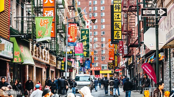 People walking in one of the colourful streets in NY Chinatown.