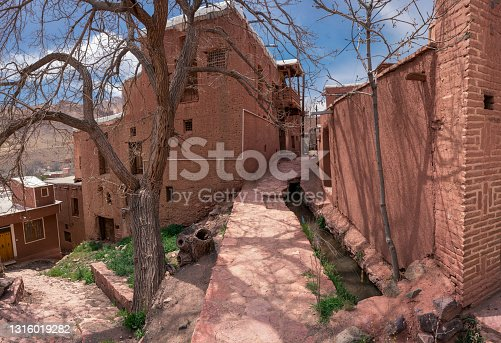 Streets of famous old Iranian village of Abyaneh. Barzrud Rural District, in the Central District of Natanz County, Isfahan Province, Iran. Red clay buildings. Mud bricks. Persia.