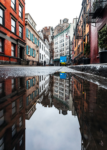 Streets of Greenwich Village reflected in puddle. New York City, USA