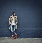 Portrait of a fashionable young man wearing urban wear and posing against a gray wall