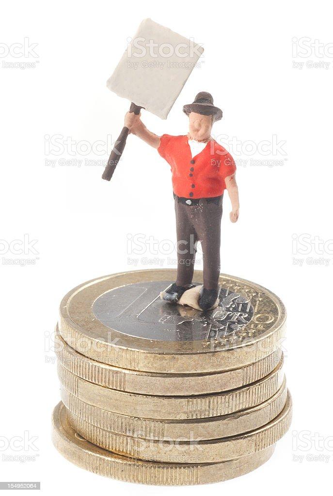 Streikendes Männchen mit Schild auf Euromünzen stock photo