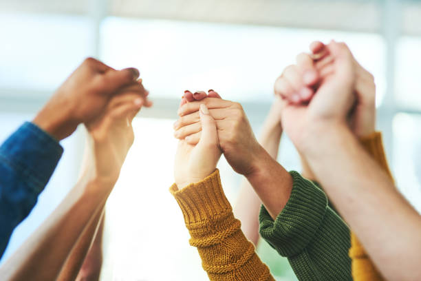 Strength in numbers Closeup shot of a diverse group of people holding hands together in unity group therapy stock pictures, royalty-free photos & images