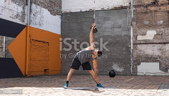 Strong athletic man working out with a kettlebell, gym concept.