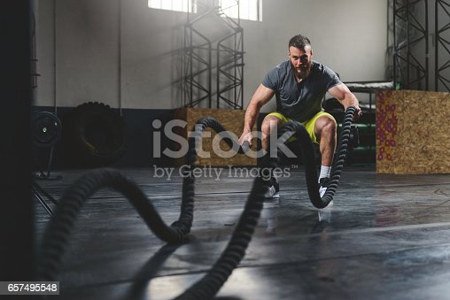 Shot of a man training with heavy ropes at the gym.