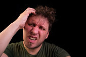 Stress. A man holds his head with his hands.