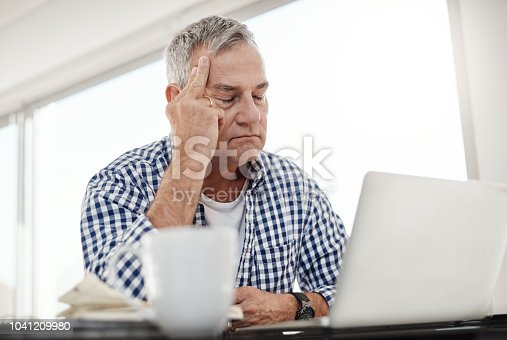Shot of a mature man looking stressed out while working on a laptop at home