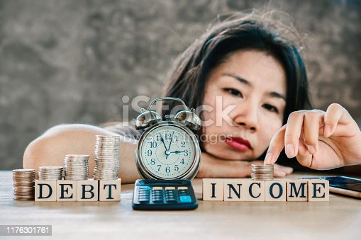 1018458132istockphoto stress Asian woman having problem with imbalance income and debt  ,counting money on desk 1176301761