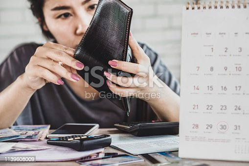 stress Asian woman open empty wallet looking for money for debt with bills, deadline calendar on desk
