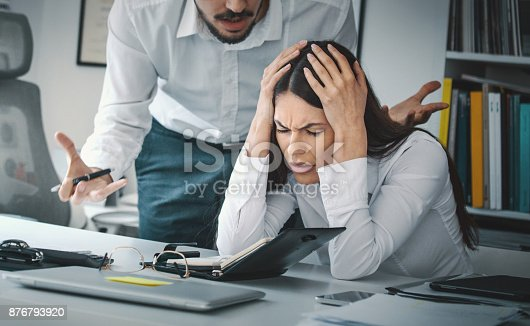 Closeup of late 20's employee at a computer company being criticized by her boss which is giving her a headache.