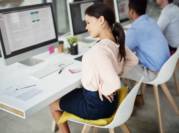 Stress, bad for her back and bad for business Shot of a young businesswoman experiencing back pain while working at her desk in a modern office bad posture stock pictures, royalty-free photos & images