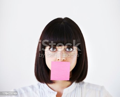 Conceptual image of a young businesswoman with a pink post-it note covering her mouth